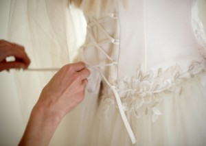 Lacing a wedding gown to get the right fit.