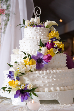 White Wedding Cake with Purple and Yellow Flowers and Single Monogram Cake Topper